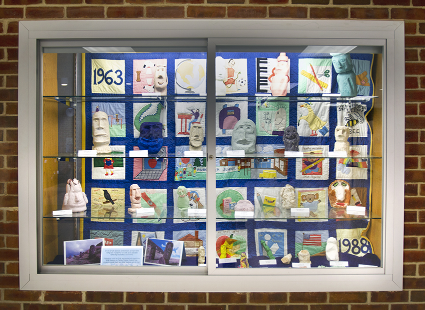 Photograph of the display case in the lobby of Ravensworth Elementary showing a hand-sewn patchwork quilt.