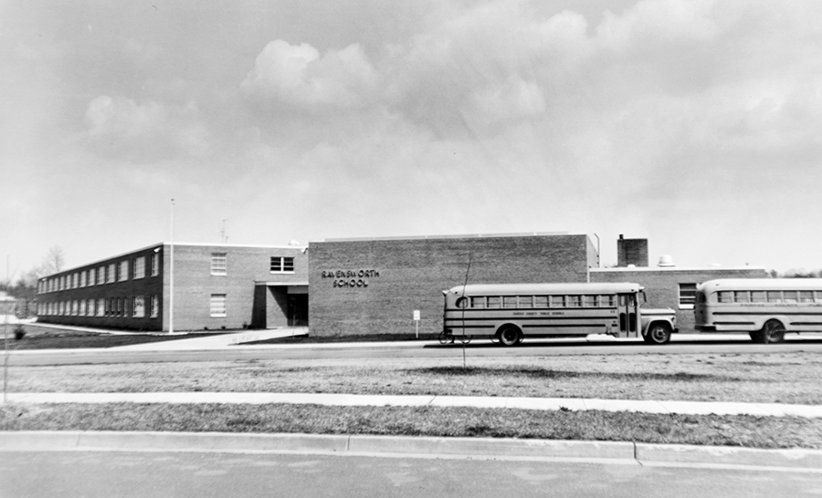 Black and white photograph of Ravensworth Elementary School taken around 1966 before the first addition was constructed. Two school buses are parked in front of the building.