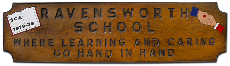 Photograph of a large wooden sign that formerly hung in Ravensworth Elementary School. The sign was donated by Ravensworth's student council association during the 1978 to 1979 school year. It reads, Ravensworth School, Where Learning and Caring Go Hand in Hand.